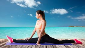 Smiling woman doing splits on mat over sea Royalty Free Stock Photography