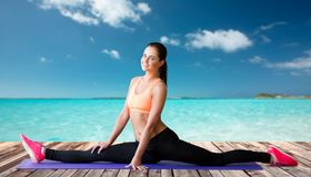 Smiling woman doing splits on mat over sea Stock Photography