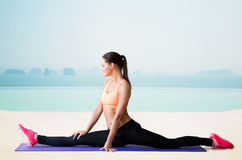 Smiling woman doing splits over sea and pool Stock Photo