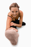 Smiling woman doing stretches on the floor. Against a white background Stock Photo