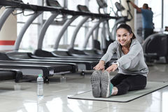 Smiling woman doing stretching exercises Stock Images