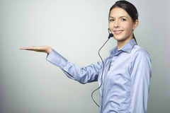 Smiling woman doing telemarketing. Smiling attractive, friendly woman doing telemarketing or a promotion wearing a headset and extending her empty palm for your Stock Images