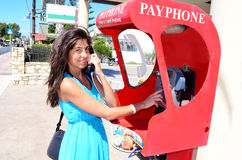 Smiling  woman is doing a telephone call inside a telephone box. Royalty Free Stock Images