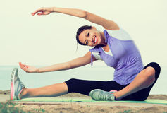 Smiling woman doing  workout on sea beach Royalty Free Stock Photography