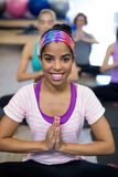 Smiling woman doing yoga in gym royalty free stock image