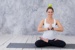 Smiling woman doing yoga pose holding apple on her head.  Royalty Free Stock Images