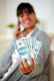 Smiling woman with dollars talking on mobile phone Royalty Free Stock Image