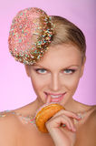 Smiling woman, donut on head and front of mouth Royalty Free Stock Image