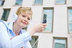 Smiling woman downloading music with smartphone Royalty Free Stock Image