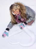 Smiling woman draw heart on snow Royalty Free Stock Photography