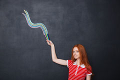 Smiling woman drawing wave with colorful pencils on blackboard background Stock Photos
