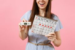 Smiling woman in dress hold in hand thermometer, female periods calendar for checking menstruation days isolated on pink. Background. Medical healthcare stock photos