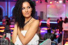 Smiling woman in dress looks away in night club. Royalty Free Stock Images