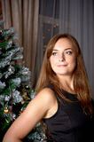 Smiling woman in dress over christmas tree Royalty Free Stock Photography