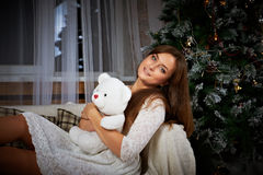 Smiling woman in dress over christmas tree Stock Photo