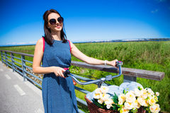 Smiling woman in dress posing and vintage bicycle with wicker ba Royalty Free Stock Image