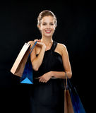 Smiling woman in dress with shopping bags Royalty Free Stock Image