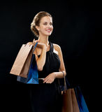 Smiling woman in dress with shopping bags Stock Image