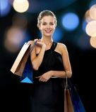 Smiling woman in dress with shopping bags Stock Photo