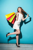 Smiling woman in dress walking with colorful shopping bags Stock Images