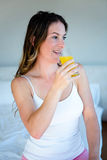 smiling woman driinking a glass of orange juice Royalty Free Stock Photography
