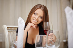 Smiling woman drinking aperitif in restaurant Stock Photo