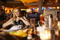 Smiling woman drinking in a cafeteria Royalty Free Stock Photos
