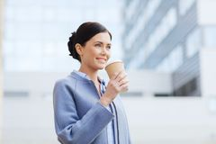 Smiling woman drinking coffee in city Royalty Free Stock Photography
