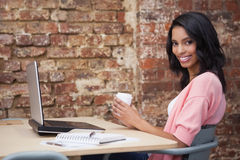 Smiling woman drinking coffee at her desk using laptop Stock Images