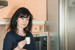 Smiling woman drinking  coffee  at kitchen Royalty Free Stock Photos