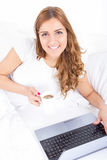 Smiling woman drinking coffee lying on bed using laptop computer Royalty Free Stock Images