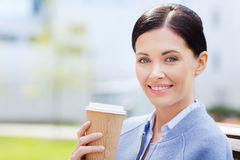 Smiling woman drinking coffee outdoors Stock Photo