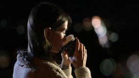 Smiling woman drinking coffee outdoors at night stock footage