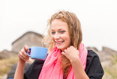 Smiling woman drinking coffee outdoors Royalty Free Stock Image