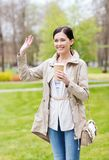 Smiling woman drinking coffee in park Royalty Free Stock Photography