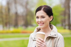 Smiling woman drinking coffee in park Royalty Free Stock Photos