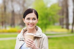 Smiling woman drinking coffee in park Royalty Free Stock Image