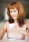 Smiling woman drinking coffee Royalty Free Stock Images