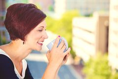 Smiling woman drinking coffee in sun sitting outdoor Stock Photos