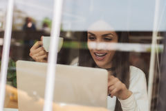 Smiling woman drinking coffee and surfing on internet. Cafe wind Royalty Free Stock Photography