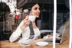 Smiling woman drinking coffee and surfing on internet. Cafe wind. Portrait of smiling woman drinking coffee and surfing on internet. Cafe window Stock Photography
