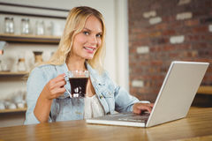 Smiling woman drinking coffee and typing on laptop. Portrait of smiling woman drinking coffee and typing on laptop at coffee shop Stock Image