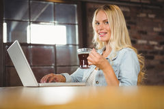 Smiling woman drinking coffee and typing on laptop. Portrait of smiling woman drinking coffee and typing on laptop at coffee shop Stock Photo