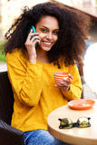 Smiling woman drinking coffee and using mobile phone Stock Image