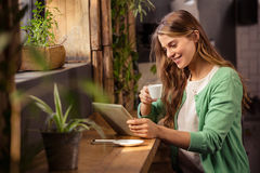 Smiling woman drinking coffee and using tablet Stock Photo