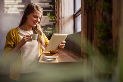 Smiling woman drinking coffee and using tablet Stock Image