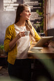 Smiling woman drinking coffee and using tablet Royalty Free Stock Photos