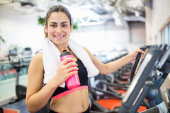 Smiling woman drinking on the cross trainer Stock Photos