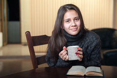 Smiling woman drinking delicious tea sitting at the table. Woman drinking tea and reading a book while sitting at table Royalty Free Stock Photography