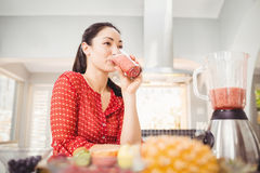 Smiling woman drinking fruit juice Stock Image